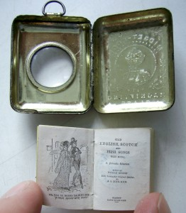 A locket with accompanying magnifying glass above the title-page and frontispiece of the score