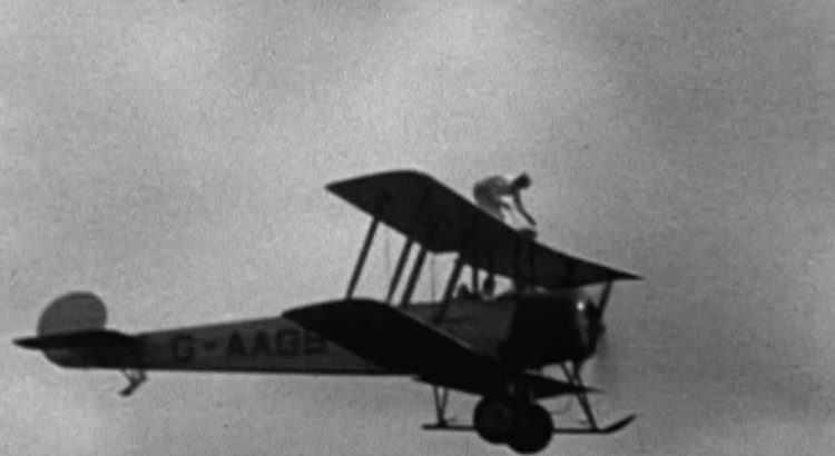 Man standing on biplane in flight