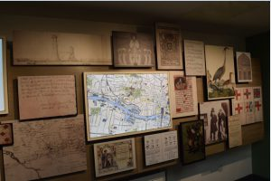 An exhibition wall of maps, drawings and documents