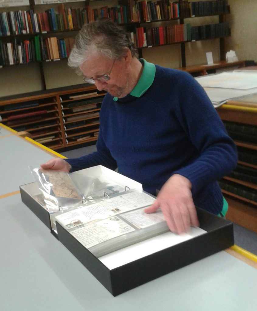 Tam Burke chuckling at one of the postcard folders.