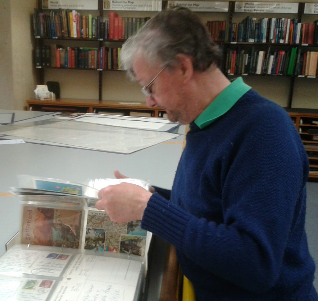 Our former colleague (Tam Burke) studies the postcard folders