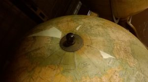 North pole of large globe showing the metal end of the axis