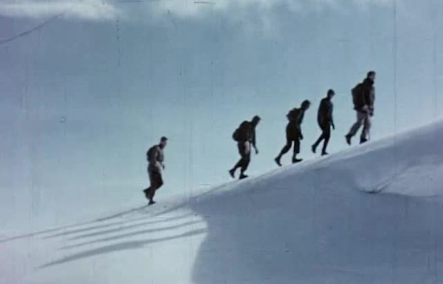 Five climbers walking up a snowy slope