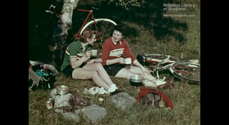 Two women are taking a break in the countryside. They are wearing sporting clothes and drinking from cups. There is a bicycle and a tree behind them.