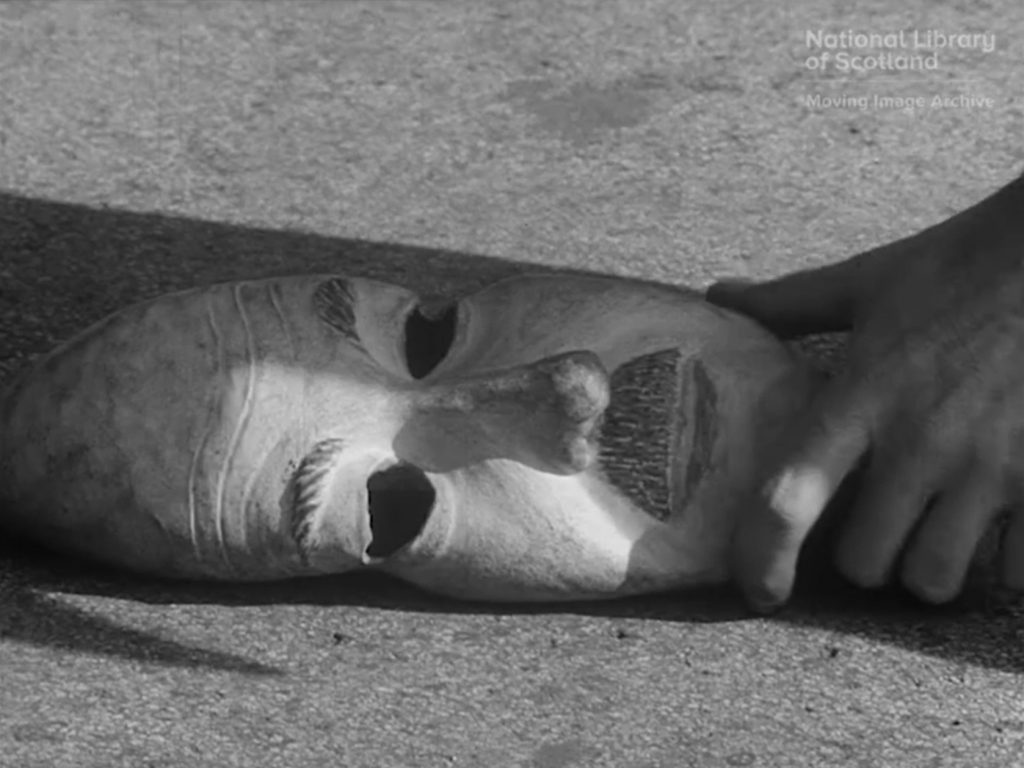 Black and white still of rubber mask on ground with a man's hand holding it