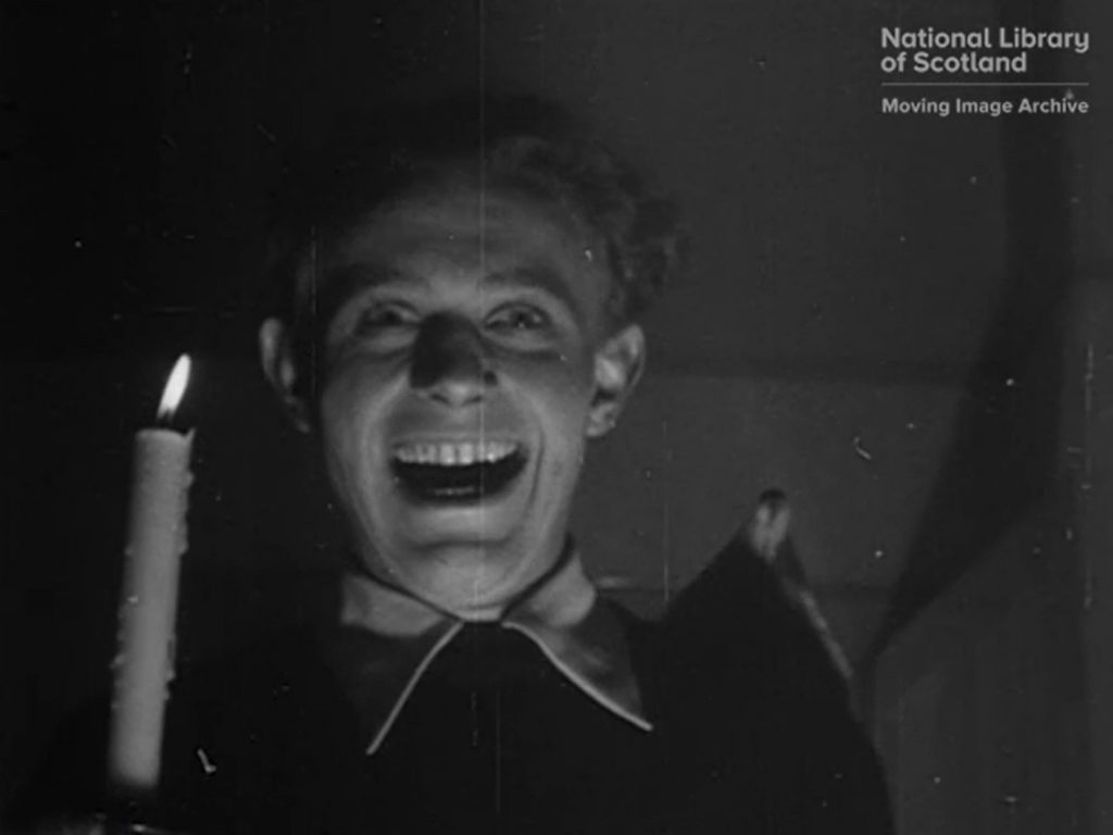 Black and white still of young man holding lit candle and laughing